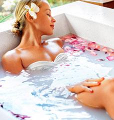 Female relaxing in bath of rose petals