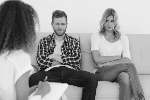 unhappy young couple sitting apart of sofa