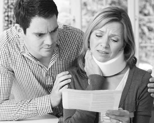 Woman in pain with neck brace reading document with her husband